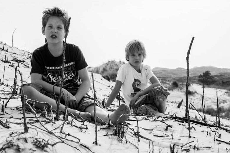Stoere kids in zwart/wit - Deze jongens zijn een stel stoere kids. Ze passen helemaal in de omgeving. Ik vind de lijnen van de takken in het zand en d