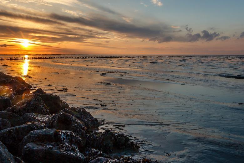 Waddenzee bij Lauwersoog - De ondergaande zon aan de Waddenzee bij Lauwersoog. Na geduldig wachten en mijn positie innemen heb ik deze foto gemaakt.