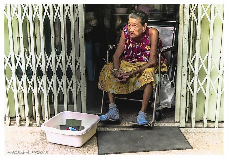 Bangkok - Tekening van een leuke oud vrouw met teiltje tussen de schuifhekken..