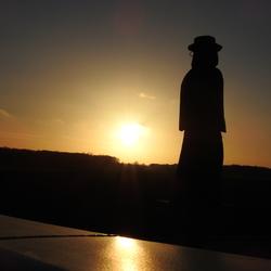 pater-damiaan met zonsondergang aan de damiaanbrug in ninde