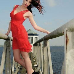 Girl in red dress posing in the wind