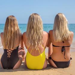 Drie blonde meisjes zitten op het strand