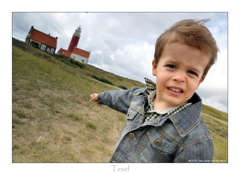 Job op Texel - Zoontje Job wijst trots naar de vuurtoren, welke hij een dag eerder nog had beklommen.<br /> In zijn rechterhand heef hij een miniatuu