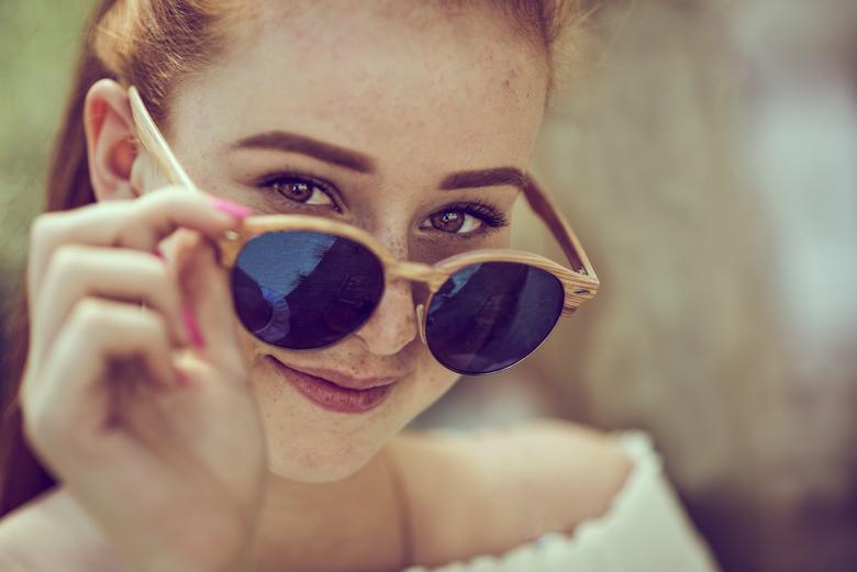 zonnenbril - dame met bril  waar ze over heen kijkt