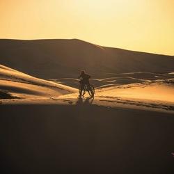Fietser in woestijn van Merzouga