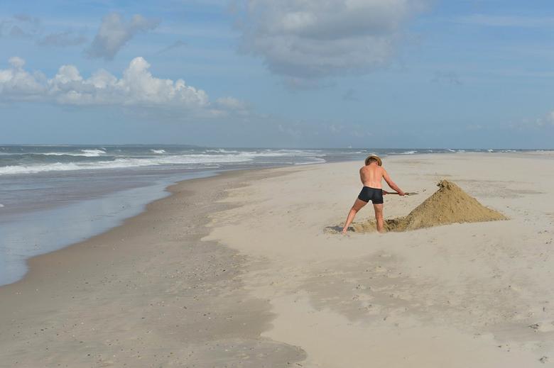 Wie een kuil graaft... - Terwijl aan onze westkust de stranden bomvol liggen, waan je je op Vlieland alleen op de wereld...