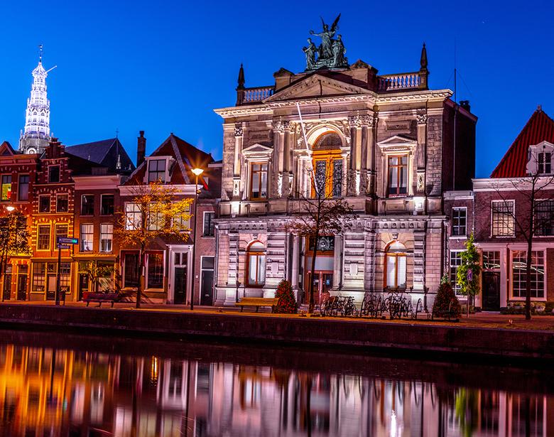 Teylers-Museum - Het Teylers Museum aan het Spaarne in Haarlem tijdens het blauwe uurtje. de toren van de Bavo met de nieuwe (led) verlichting staat e