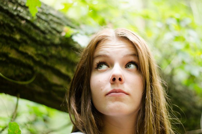 lady in the woods - foto gemaakt met heel zacht ligt onder een bladerdek en bij een omgevallen begroeide boom.
