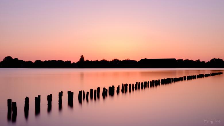 Waterlandschap, zonsondergang en paaltjes