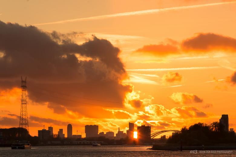 Sunset Rotterdam City - De zon verdwijnt achter de Rotterdamse skyline, een fenomenale wolkenlucht achterlatend. Foto genomen vanaf de Lekkade in Kind