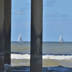 Schildering tussen de palen van de pier in Scheveningen