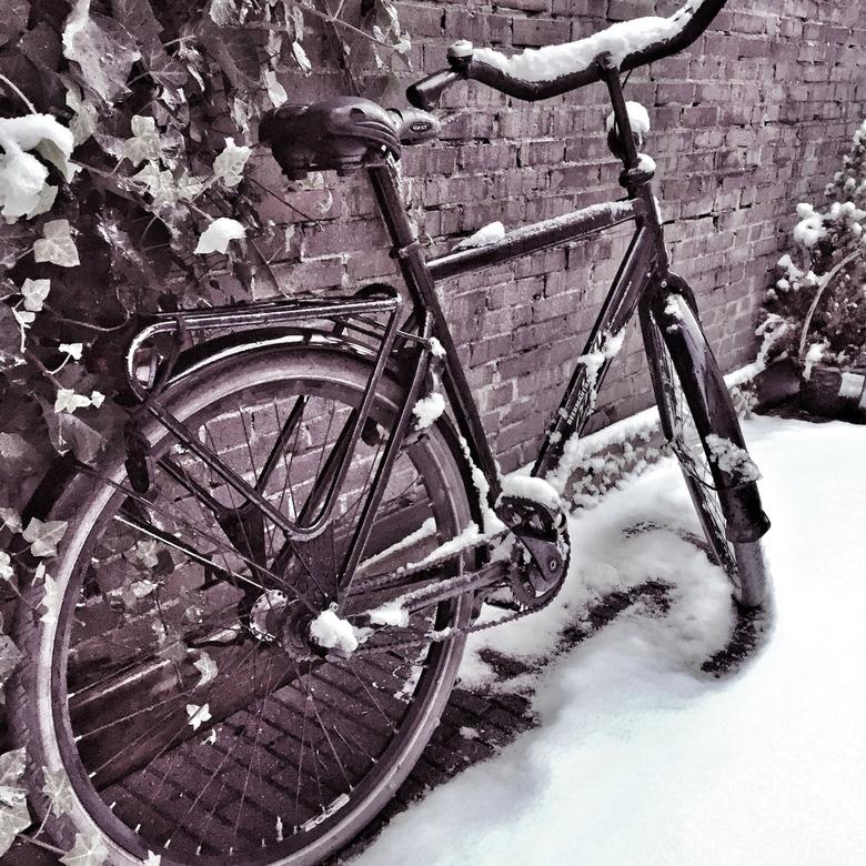 Te koud om te fietsen - Fiets tegen een stenen muur in de sneeuw