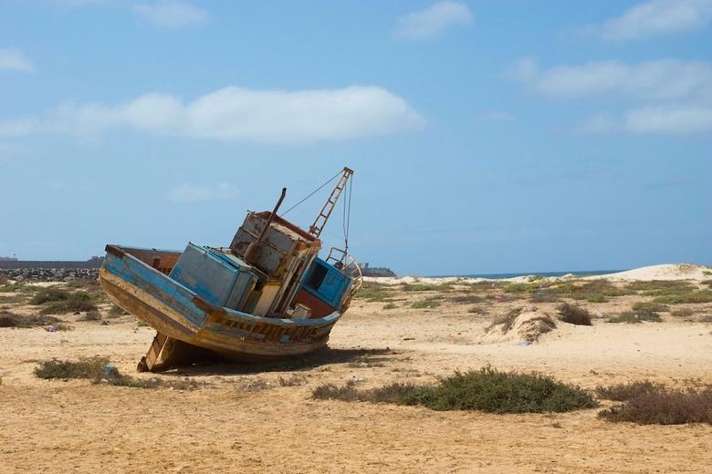 Eenzaam en verbannen - Eenzaam en verlaten schip op het strand nabij een stadje ergens in Afrika