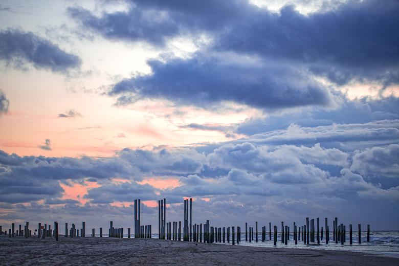 Palendorp Petten (NH) - Dramatische luchten op een avond in november. Het Palendorp steekt af tegen de grijze wolken en de zon probeert nog een beetje