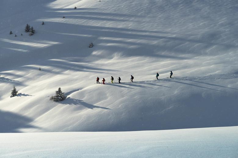 The great white open - Een kleine groep skiers onderleiding van een ervaren gids zijn offpiste om de afdalingen te verkennen, een prachtig gezicht.