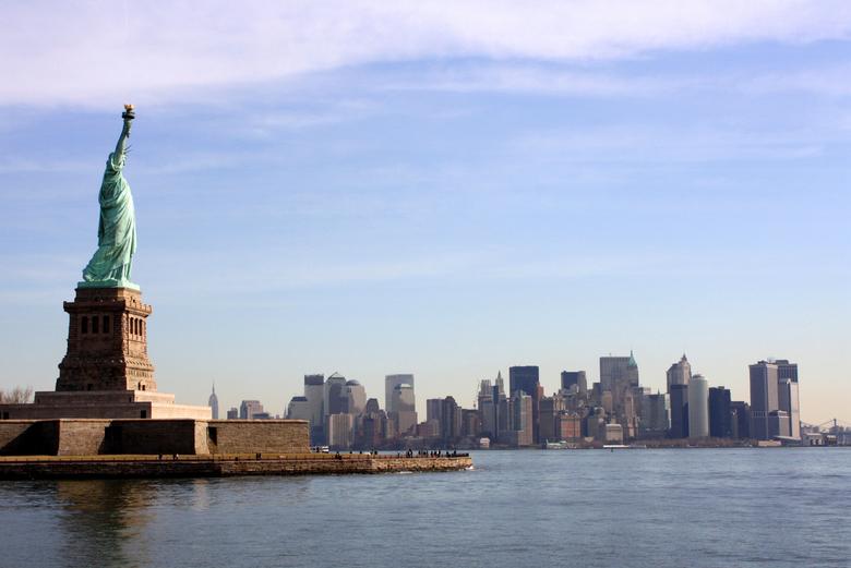 New York City: Lady Liberty - Deze foto is genomen vanaf de boot die langs Liberty Island voer. Zowel de New York skyline als het Vrijheidsbeeld zijn