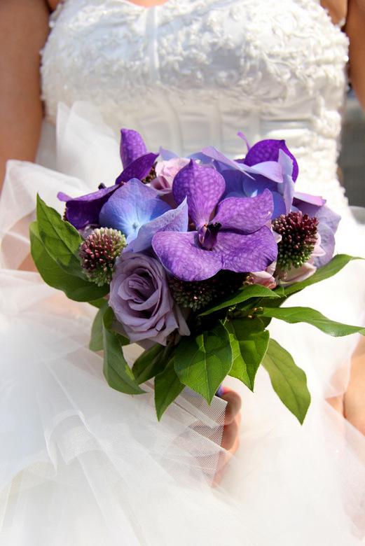 Het bruidsboeket - Bruid houdt haar paars kleurige boeket vast tijdens haar trouwdag