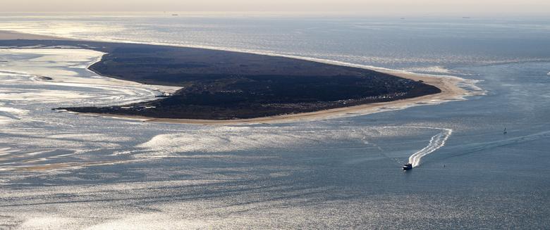 Vlieland in tegenlicht - Vlieland in tegenlicht. Het eiland vanuit het zuidoosten boven de Waddenzee in het tegenlicht van de avondzon. Op de voorgron