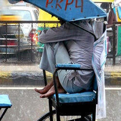 Riksha-rijder in regen