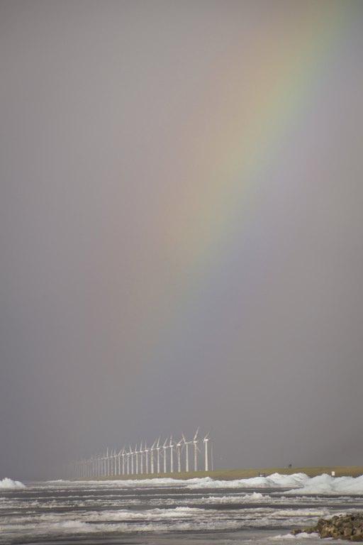 Windmolens en regenboog - Kruiend ijs langs het ijsselmeer met een regenboog achter de windmolens.