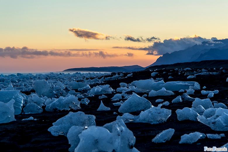 Sunset at Jökulsárlón, Iceland - Dit is het strand bij het bekende Jökulsárlón in IJsland tijdens zonsondergang. Het hele strand is bezaaid met ijsblo