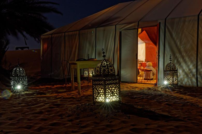 Nacht in Merzouga - Een nachtje in de woestijn bij Merzouga. Er is een bedouinentent klaar gezet voor de avond. Verlichting geeft de weg aan.