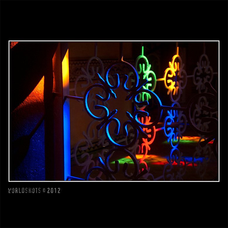 kleurig smeedwerk - Mooi verlicht smeedijzeren hek in een huis (Marokko), beschenen door het zonlicht dat door een glas-in-lood-raam naar binnen viel