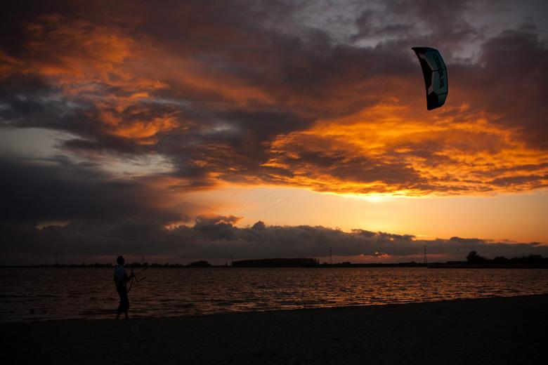 Kitesurfing bij ondergaande zon - Verwoede eerste pogingen om te kitesurfen, en ik maar lopen om de mooiste positie te krijgen.<br /> ach je moet er