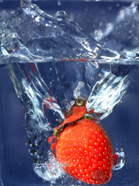 plons - aardbei valt in water
