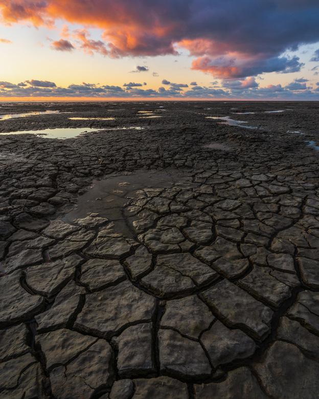 Cracks of the Earth II - Zonsondergang bij de moddervlaktes aan de Waddenzee in Friesland.