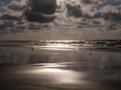 strand - Dreigende luchten en de weerkaatsing van de zon op het natte zand