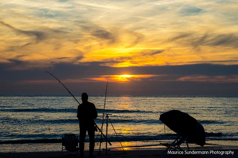 Visser op een zomeravond - Een visser gefotografeerd tijdens zonsondergang op De Maasvlakte 2.<br /> Het was een zomeravond met aparte bewolking.
