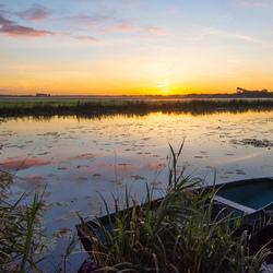 Boot in water tijdens zonsopkomst.