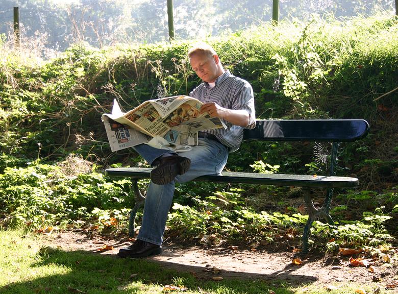 Ochtendkrant - Lekker met de ochtendkrant in de zon. Ondanks het tegenlicht wordt het gezicht nog mooi belicht door de reflectie in de krant. De dauwd