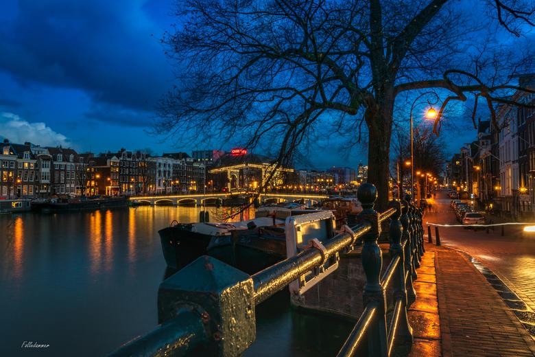 De Amstel by night - Een lange sluitertijd foto van de Amstel en de Magere Brug in de verte. <br /> Deze heeft hier al eerder gestaan, maar die heb i