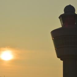 Luchtverkeerstoren Schiphol met ondergaande zon