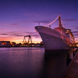 De SS Rotterdam in het avondlicht