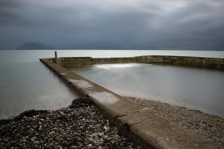 Getijdebad, Wales - Getijdezwembad in Wales. Er was een mooie duistere lucht, regen dreigde. Het was guur weer; er waren weinig mensen. Alle tijd om t