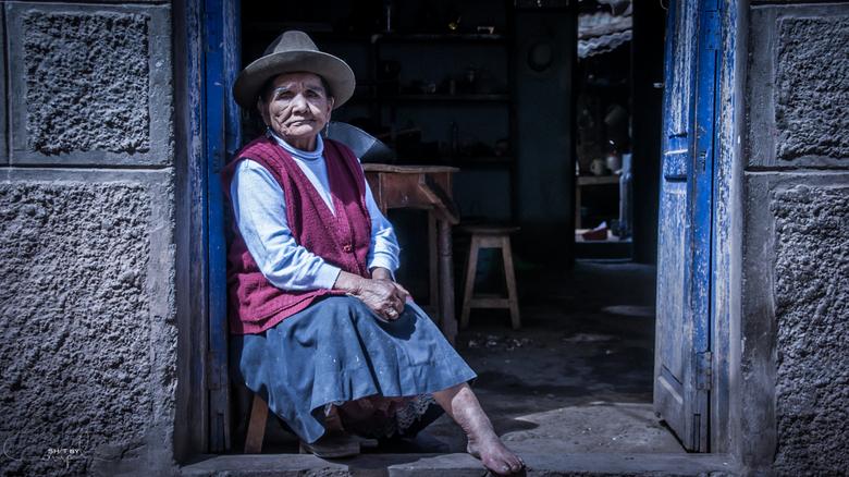 Sitting - Beeld van een vrouwtje in de opening van haar huisje.