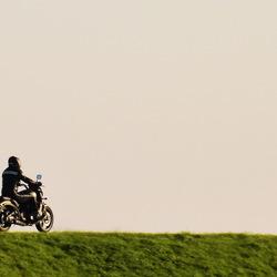 Eenzame motorrijder op de dijk