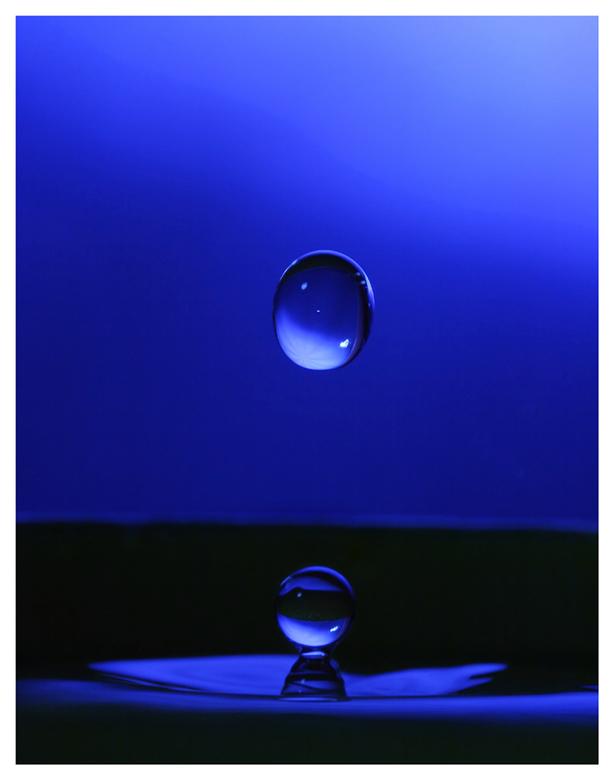waterdruppel - een vallende waterdruppel met een donkerblauwe achtergrond