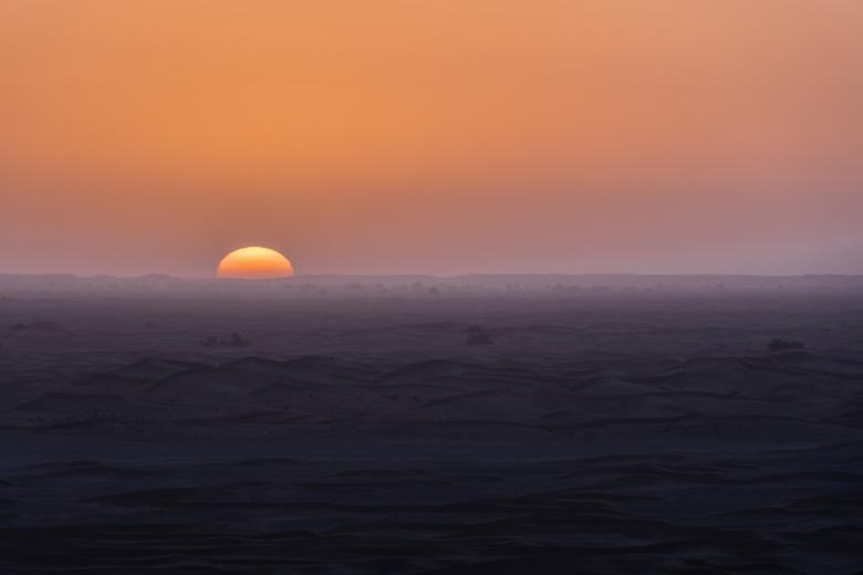 Scaring Away the Cold - Zonsopkomst in de Sahara in Marokko. Genomen vanaf een hoog duin naast onze kampeerplek. Bewust de horizon in het midden gelat