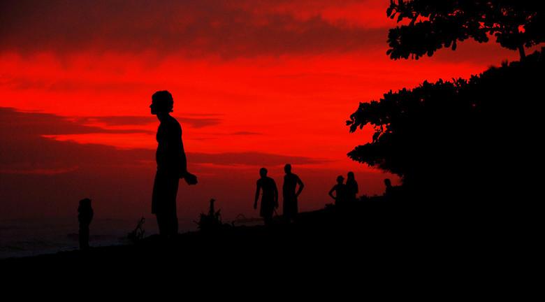 Silhouetten - Silhouetten van toeristen en locals tegen een fel rode lucht tijdens de zonsondergang in Dominical, Costa Rica (2008). De mensen op het