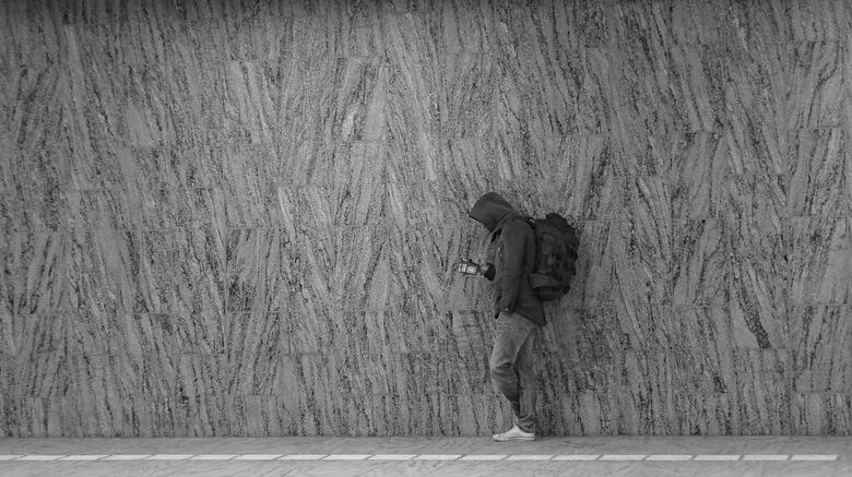 rustpuntje - deze foto vind ik intrigerend. wat is deze jongen met zijn smartphone aan het doen.hij staat op 1 been volledig relaxt tegen een eentonig