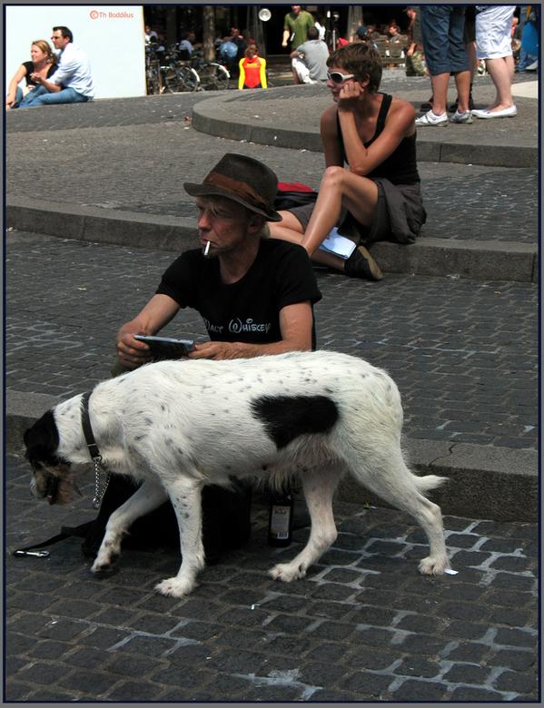 op de dam van Amsterdam  - een man met zijn 2 beste vrienden : Zijn hond en de fles ..