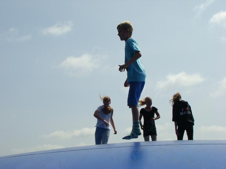 Kinderen op springkussen - Kinderen springen op een luchtkussen in een speeltuin