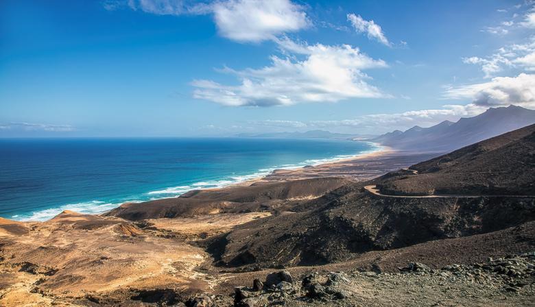 Adembenemend  - is het uitzicht vanaf het Punto de vista sobre puerto de montaña over de vulkanische bergen van het schiereiland Jandía en het kilomet
