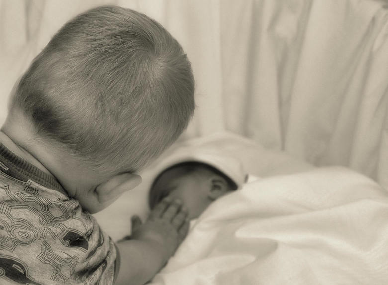 Tederheid - grote broer geeft zijn pas geboren zusje een aai over de wang