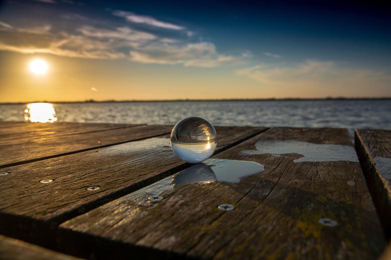 Zonsondergang op de steiger - Glazen bol op de steiger tijdens zonsondergang