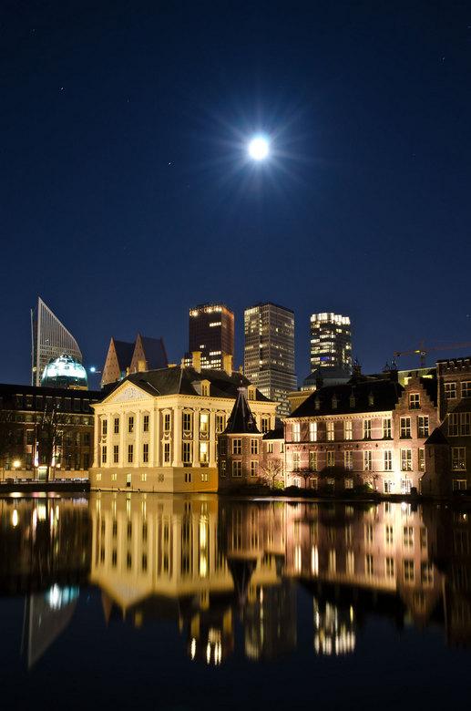 Den Haag weerspiegeld in hofvijver - Het Mauritshuis en het torentje van het binnenhof worden tijdens volle maan in de hofvijver weerspiegeld met de m